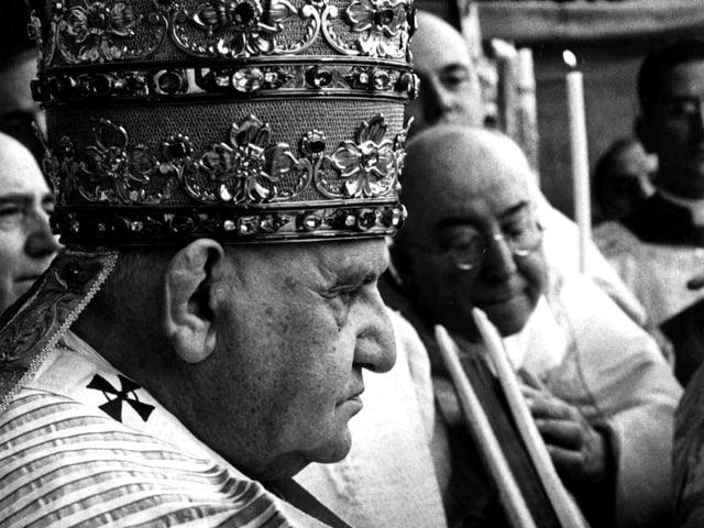 Johannes XXIII. von der Seite, er wird zum Papst gekrönt. Ein schwarzweiss-Foto. Er trägt einen massiven Kopfschmuck.