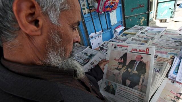 Ein Mann hält eine Zeitung in der Hand.