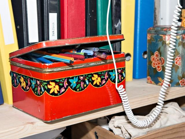 Rote Kiste mit Stiften in einem Regal mit Ordnern. Davor hängt ein Telefonkabel.