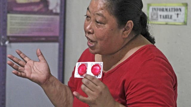 Eine Frau zeigt Kondome.