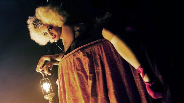 Frau mit barock anmutender Perücke schaut lasziv in die Kamera.