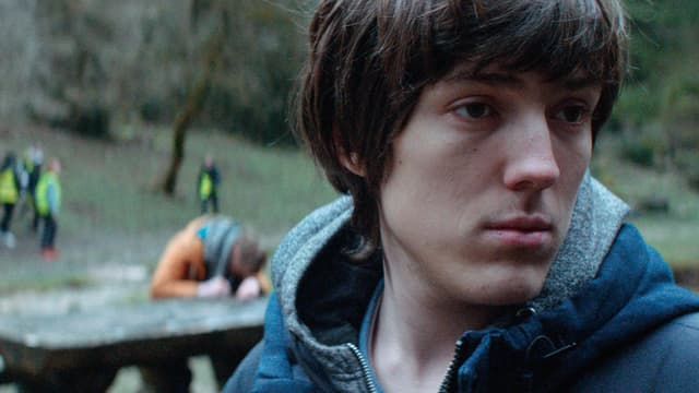 Ein Junge im Wald. Er schaut nach rechts.