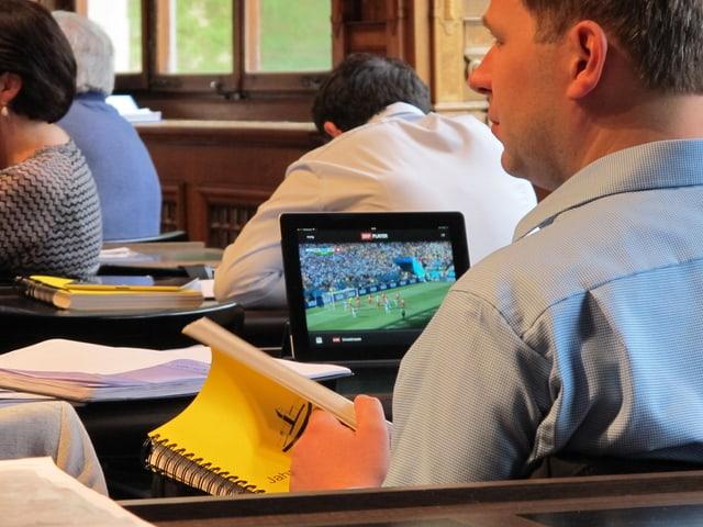 Ein Politiker blättert in der Stadtrechnung, während auf dem Computer vor ihm ein Fussballspiel läuft.