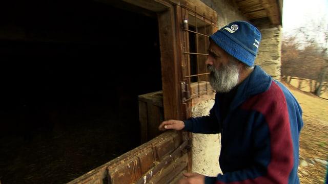 Bauer steht vor Stall
