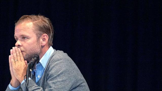 Christian Kracht sitzend vor einem Mikrofon.