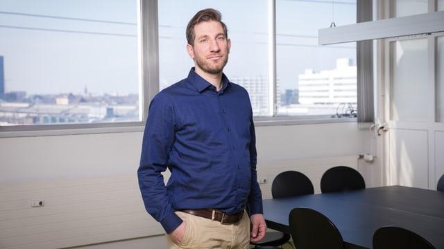 Ein ernst aussehender, junger Mann steht in einem Konferenzraum.
