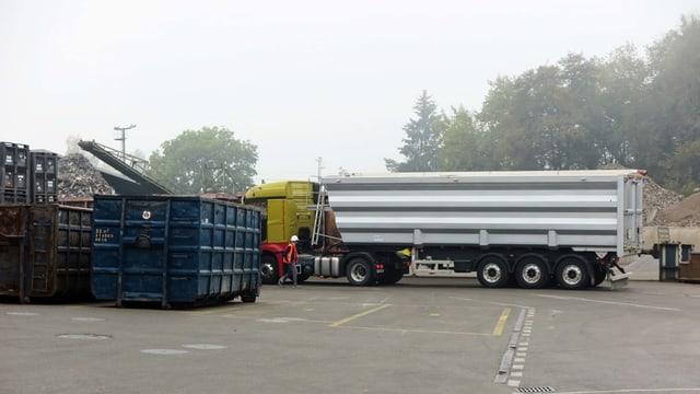 Lastwagen und Container stehen auf einem Recyclinghof
