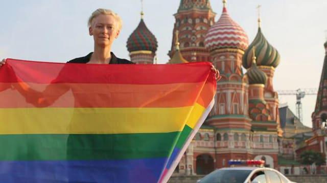 Tilda Swinton mit der Regenbogen-Flagge vor dem Moskauer Kreml stehend