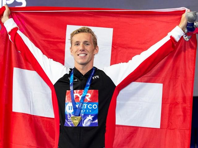 Jérémy Desplanches posiert mit einer überdimensionalen Schweizer Fahne.