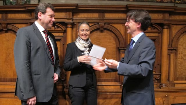 Ratspräsident Raphaël Rohner schüttelt den abtretenden Stadträten Peter Käppeler und Jeanette Storrer die Hand.