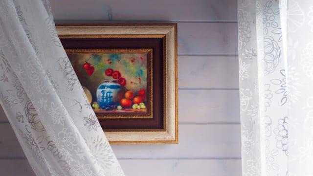 Ein Bild an einer Wand. Ein weisser Vorhang hängt drüber.