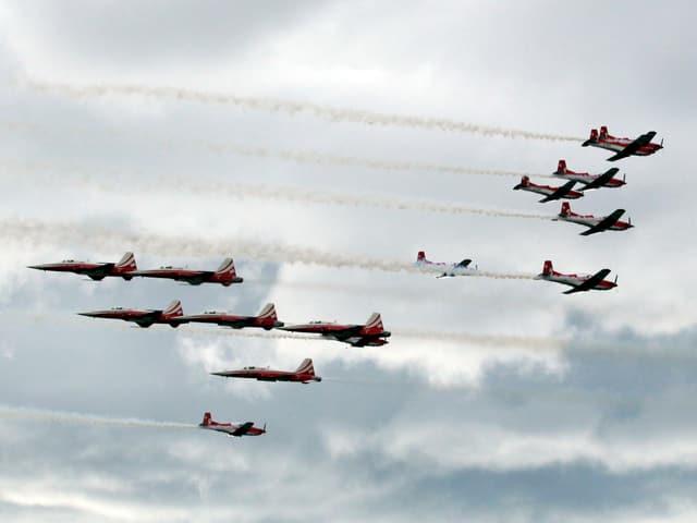 Zwei Kunstflugstaffeln kreuzen sich: Rechts die Propellermaschienen des PC-7 Teams, links die Jets der Patrouille Suisse. Alle Flugzeuge in rot/silber/weiss. Der Himmel ist bewölkt.
