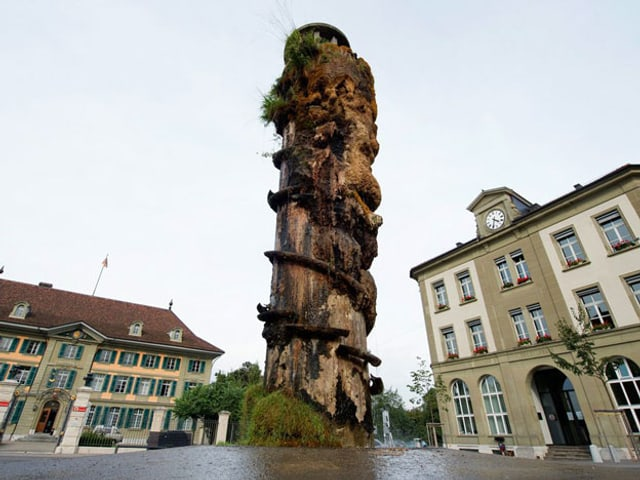 Ein Turm auf einem Platz, der bereits ziemlich verwittert und mit Moos und Pflanzen bewachsen ist.