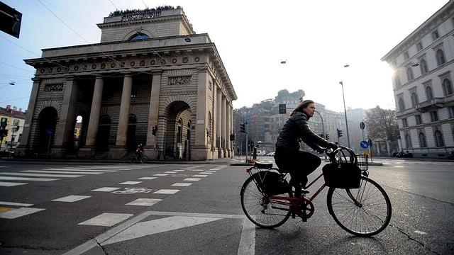 Einsame Fahrradfahrerin vor der Porta Venezia in Mailand. Keine Autos auf der Strasse.