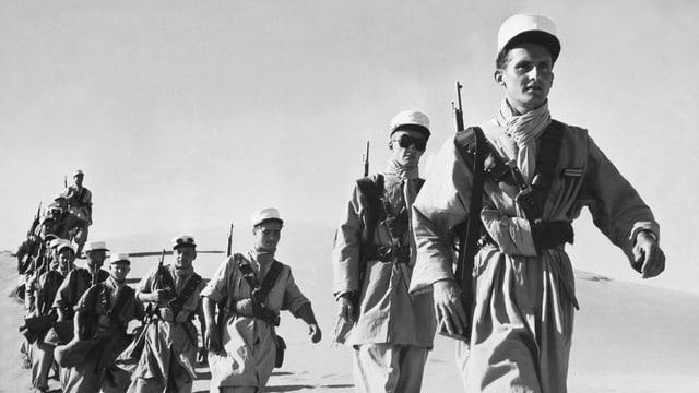 Soldaten mit geschultertem Gewehr und weissem Käppi in Einerkolonne im Wüstensand.