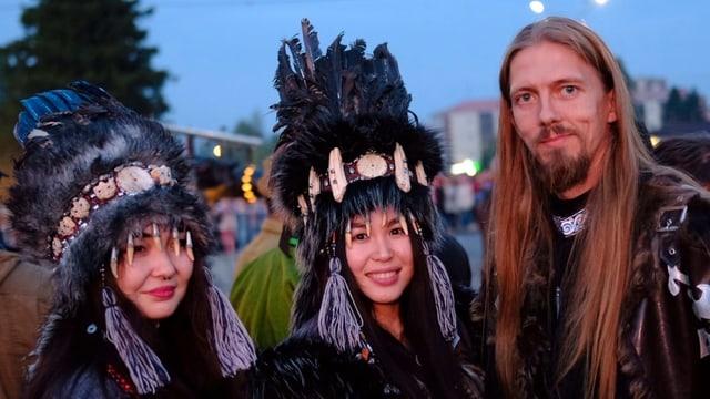 Zwei Tuwinerinnen und ein Tuwiner posieren in ihrer traditionellen Kleidung am Chomej-Festival.