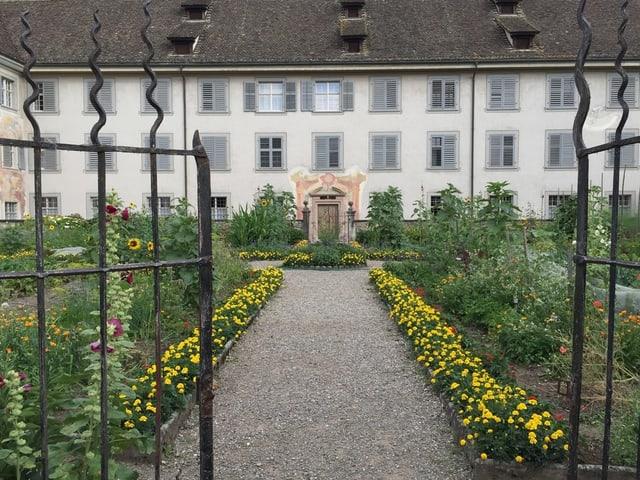 Innenhof mit Blumen, Gebäude im Hintergrund.