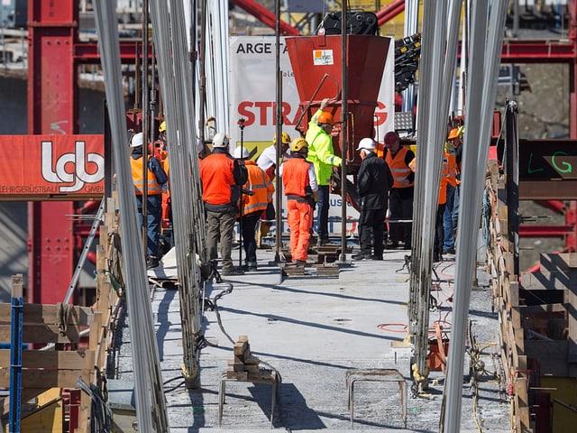 Bauarbeiter betonieren auf dem Brückenbogen.