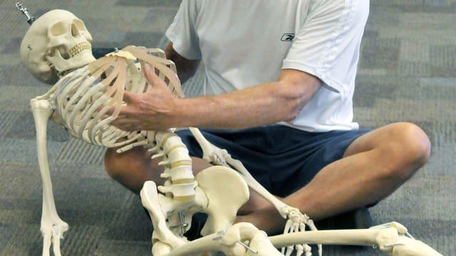 Ein Mann sitzt auf dem Boden und hält ein Skelett-Modell im Arm. Er zeigt in den Brustkorb des Skeletts.