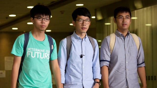 Trais giuvens asiats bandunan la dretgira a Hongkong.