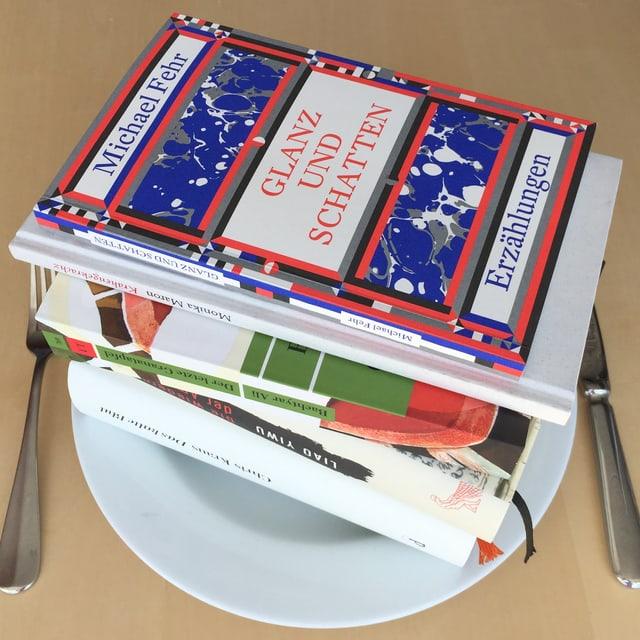 Es liegen fünf Bücher aufeinandergestappelt auf einem weissen Teller. Das Besteckt liegt daneben.