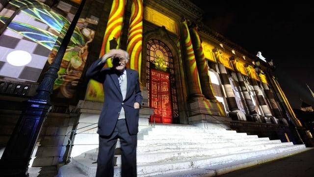 Ein älterer Herr steht vor der Fassade des Musee d'Art et d'Histoire, auf welche unterschiedliche bunte Bilder projiziert werden.