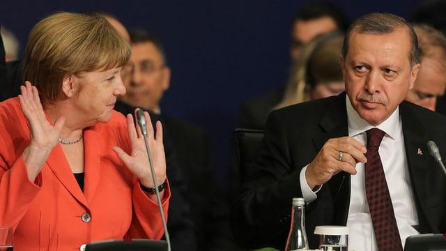 Angela Merkel (links) mit zwei erhobenen Händen sitzt neben Recep Tayyip Erdogan (rechts)