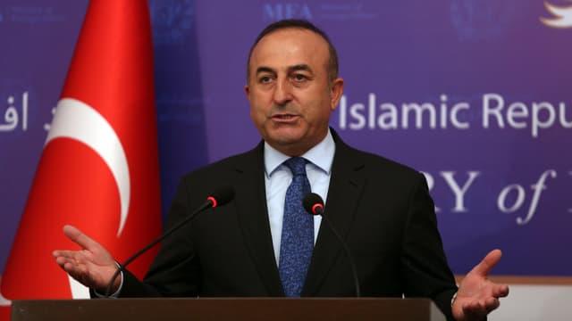 Cavusoglu bei einer Rede vor der türkischen Flagge