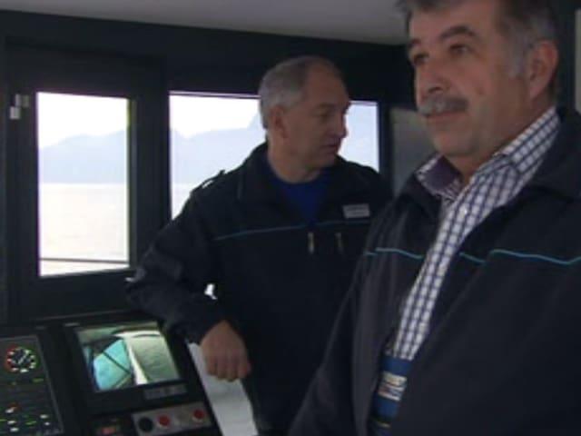 Zwei Männer in Führerkabine (auf der Brücke) des Schiffs
