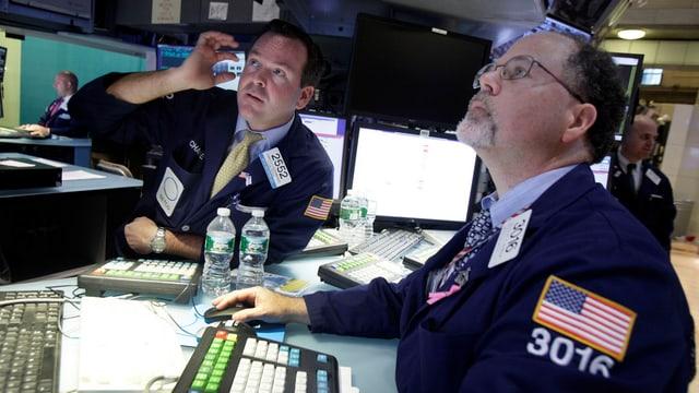 Zwei Börsenhändler schauen angespannt auf einen Bildschirm.