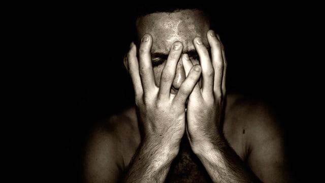 Depressiver Mann verdeckt sich das Gesicht mit seinen Händen