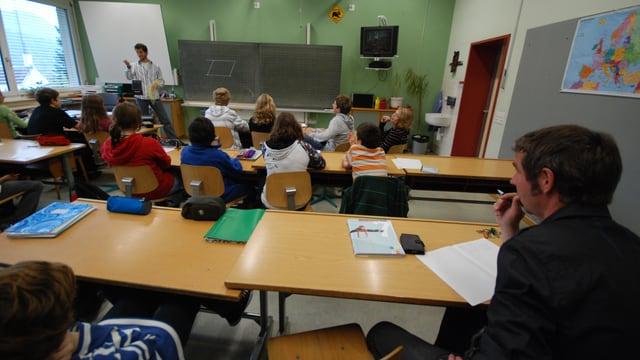Mann sitzt hinten im Klassenzimmer und beobachtet Unterricht