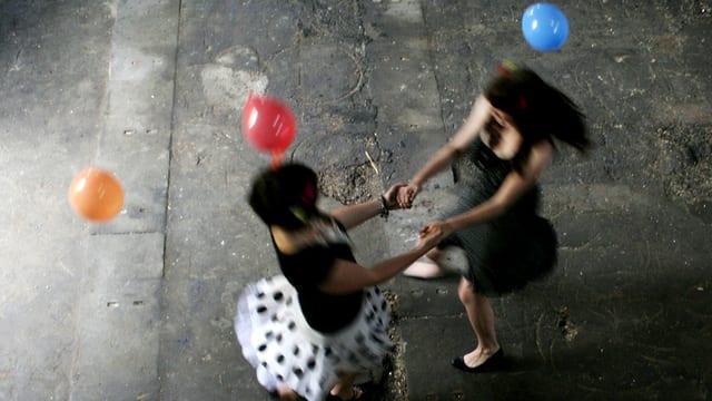 Zwei Frauen, die miteinander tanzen. Luftballons schweben in der Luft.