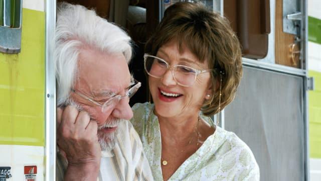 Blick auf einen Mann und eine Frau, die im Eingang eines Wohnmobils sitzen und lachen.