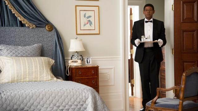 Der afroamerikansiche Butler steht mit einem Serviertablett in der Tür eines Schlafzimmers.