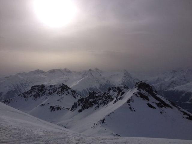Verschneite Berggipfel sind zu sehen. Darüber scheint die Sonne nur milchig mit den vielen Aerosolen in der Luft.