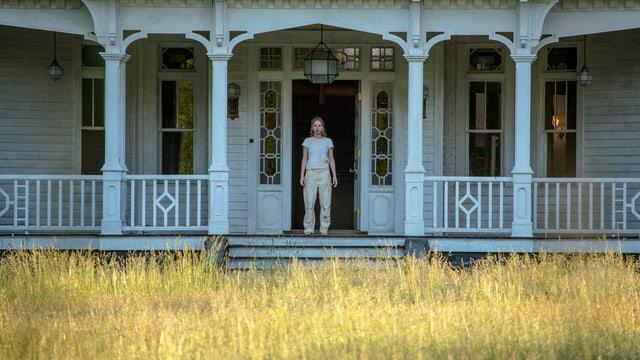 Veranda eines Hauses, dort steht eine Frau