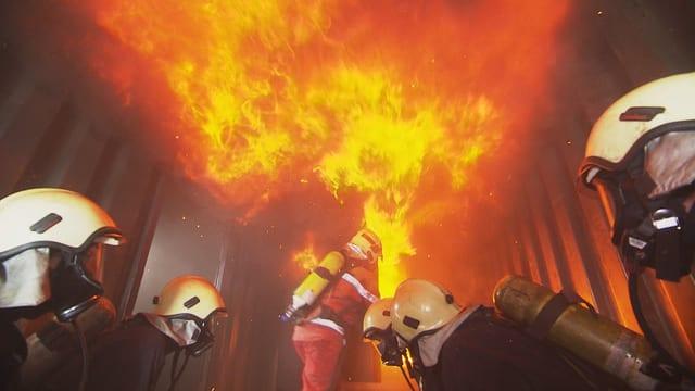 Flammen über enier Gruppe von Personen in Schutzbekleidung