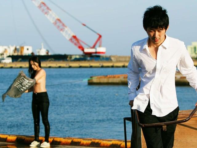 Ein Mann steht an einem Hafen, im Hintergrund sieht man eine Frau mit nacktem Oberkörper.
