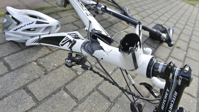 Verunfalltes Fahrrad mit gebrochenem Rahmen und einem Velohelm daneben.