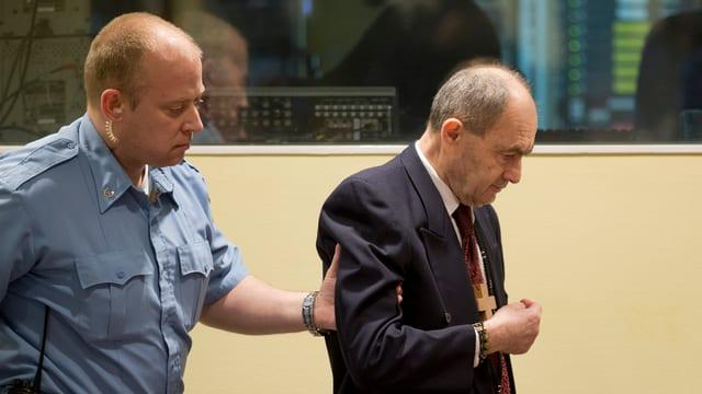 Zdravko Tolimir wird von einem Gerichtsbeamten an seinen Platz geführt.