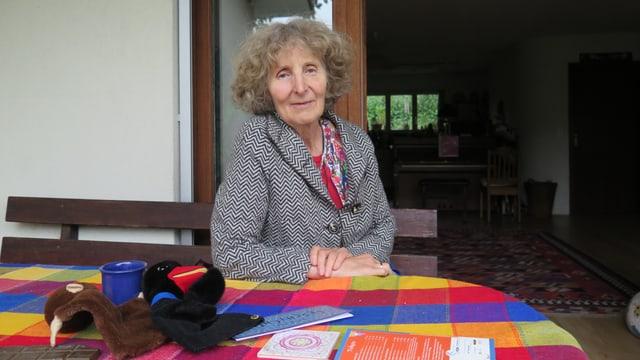 Eine ältere Dame posiert fürs Foto, Regula Waldispühl ist Märchentante. Kurze gelockte Haare, grau-weiss-kariertes Chaquet.