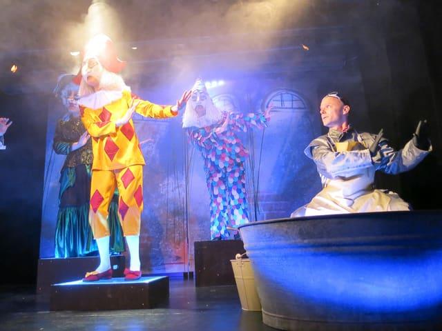 Mann sitzt bei einer Wanne und tanzt zusammen mit Blätztlibajas, alter Tante und einem Pierrot.