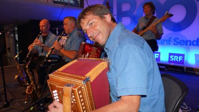 Fünf Musikanten mit Klarinette, Akkordeon, Schwyzerörgeli und Bass auf der Bühne.