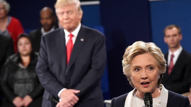 Clinton während der TV-Debatte mit Mikrofon, Trump leicht unscharf hinter ihr