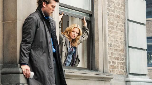 Ein Mann steht aussen an einm Fenster in luftiger Höhe. Eine Frau schaut ihn aus dem Fenster heraus an.