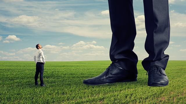 Ein kleiner Mann blickt an den Beinen eines Riesen hinauf.