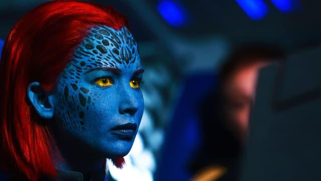 Frau mit blauem Gesicht und roten Haaren blickt in eine Richtung