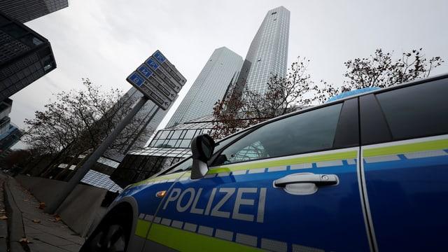 Symbolbild: Polizeiauto vor einem Wolkenkratzer der Deutschen Bank in Frankfurt.
