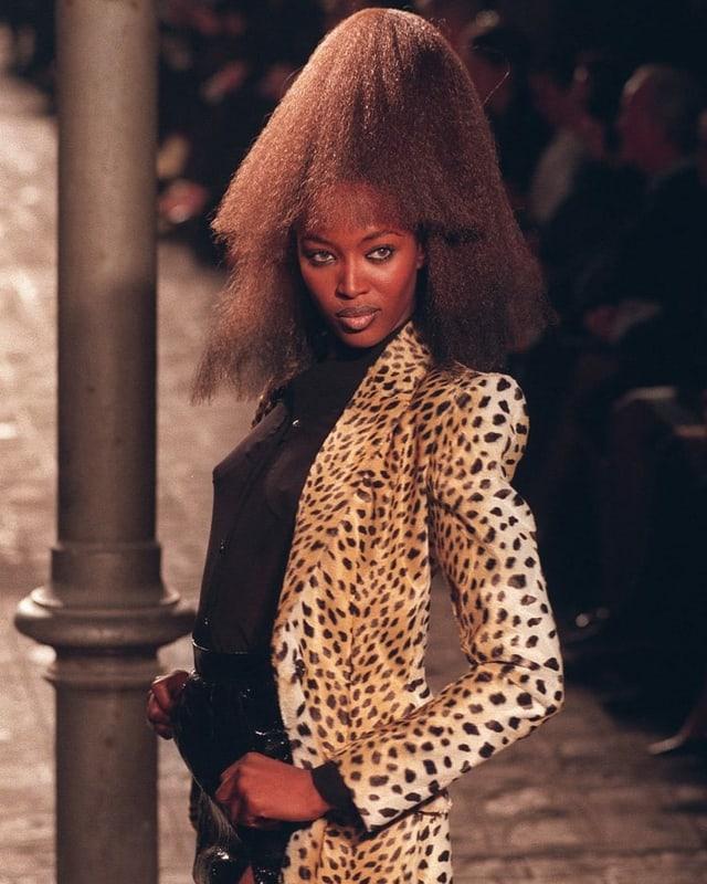 Naomi Campbell in jungen Jahren auf dem Laufsteg. Sie trägt schwarze Shorts, ein schwarzes Top und darüber ein Kurzmantel mit Leoprint. Ihre Haare sind voluminös gestylt.
